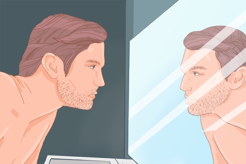 Man is checking his beard in the mirror