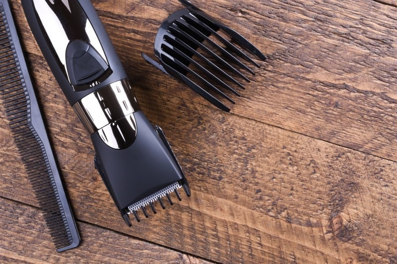 An electric razor, a brush, and a nozzle are on the wooden table