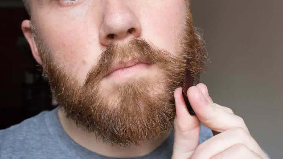 Man is combing his beard with a wooden comb