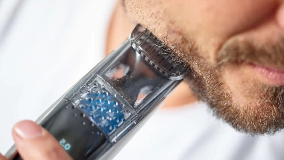 A man is trimming his beard with clippers
