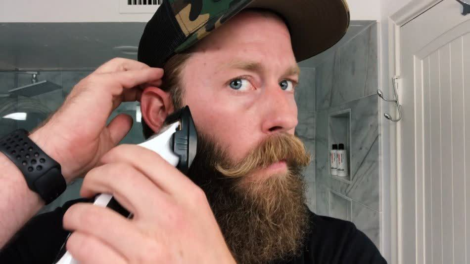 A man wearing a cap is trimming his sideburn