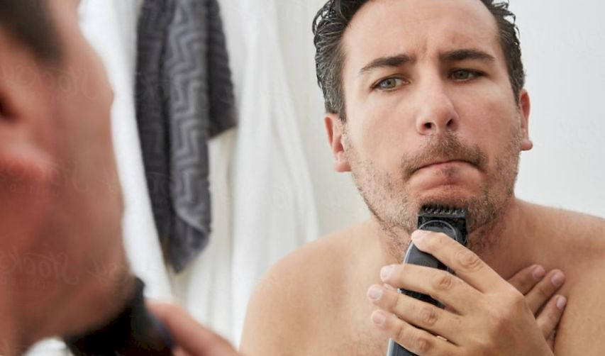 A middle-aged man is trimming his beard in the bathroom