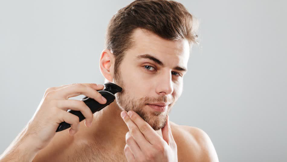 A young man is trimming his short beard