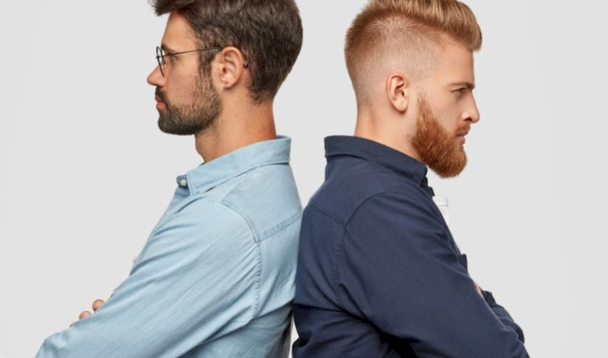 Two men with different beards are standing back to back